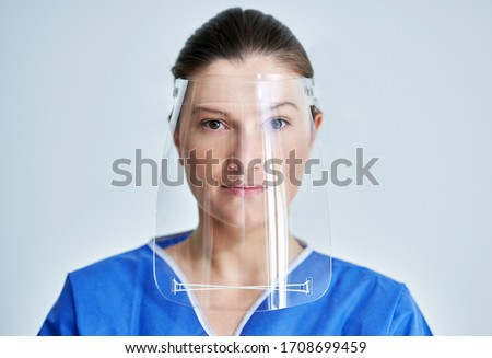 Close up portrait of female medical doctor or nurse wearing face shield Royalty-Free Stock Photo #1708699459