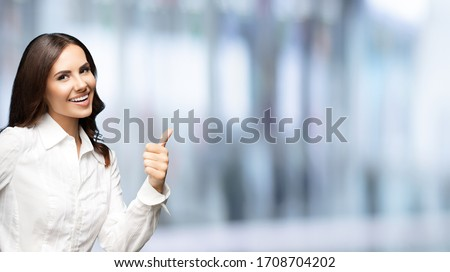 Portrait of happy smiling young excited businesswoman, showing thumb up hand sign gesture. Success in business concept studio shot. Standing against blurred office background.