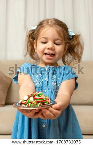 Child and traditional Ramadan candies.  Colorful sweet and baby girl.  Eid Mubarak. Kid hold plate full of sugar during Ramadan kareem (Turkish: Ramazan Bayrami). #1708732075