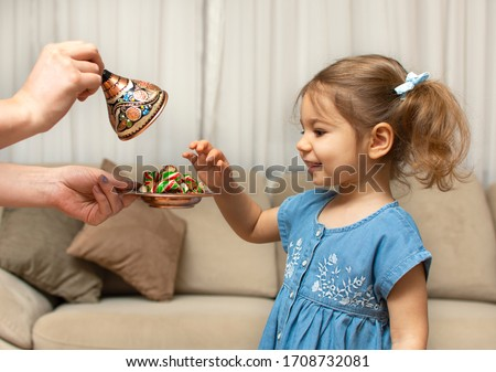 Child and traditional Ramadan candies.  Colorful sweet and baby girl.  Eid Mubarak. Kid hold plate full of sugar during Ramadan kareem (Turkish: Ramazan Bayrami). #1708732081
