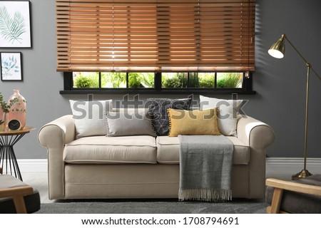 Stylish living room interior with comfortable sofa near window Royalty-Free Stock Photo #1708794691