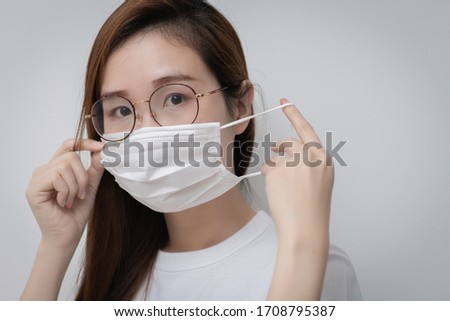 Asian Young woman in a white t-shirt and wear medical mask that protects against the spread of coronavirus or COVID-19 disease. Studio Portrait with White Background.  #1708795387