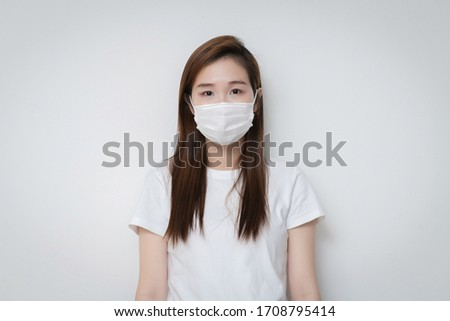Asian Young woman in a white t-shirt and wear medical mask that protects against the spread of coronavirus or COVID-19 disease. Studio Portrait with White Background.  #1708795414
