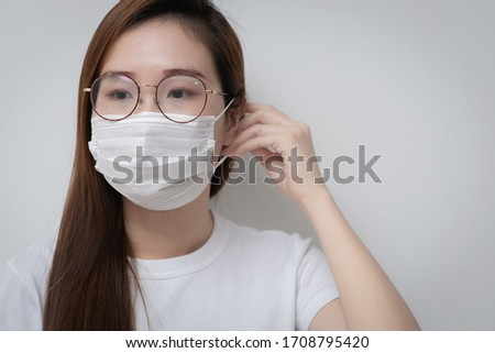 Asian Young woman in a white t-shirt and wear medical mask that protects against the spread of coronavirus or COVID-19 disease. Studio Portrait with White Background.  #1708795420