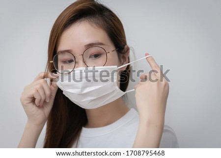 Asian Young woman in a white t-shirt and wear medical mask that protects against the spread of coronavirus or COVID-19 disease. Studio Portrait with White Background.  #1708795468