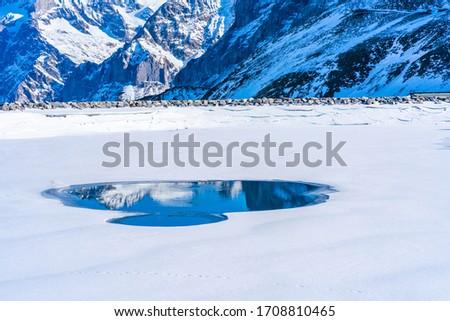 Winter landscape with snow covered peaks and frozen lake on Kleine Scheidegg mountain in Swiss Alps near Grindelwald, Switzerland #1708810465