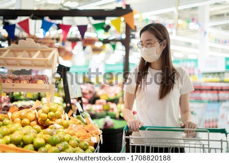 Young Asian woman wearing disposable medical mask shopping in the supermarket. during the Coronavirus COVID-19 pandemic. #1708820188