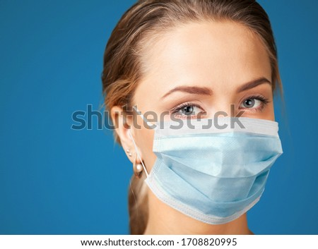 Tired female nurse, wearing a protective surgical mask #1708820995