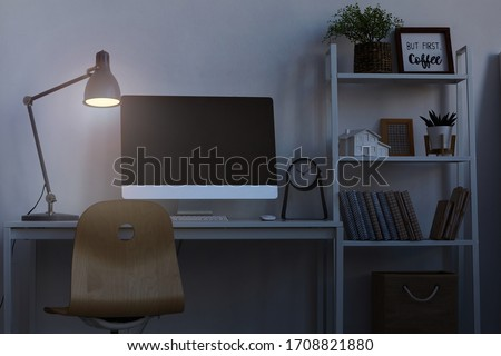 Background image of home office workplace at night, with focus on computer desk lit by dim lamp light, copy space Royalty-Free Stock Photo #1708821880