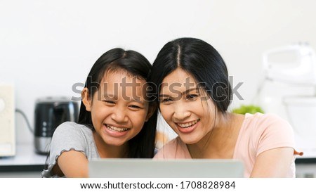 Mother and preteen daughter video call to grandparent in kitchen at home.family happy time.video conference with laptop.quarantine activity when outbreak of coronavirus.e-learning concept #1708828984