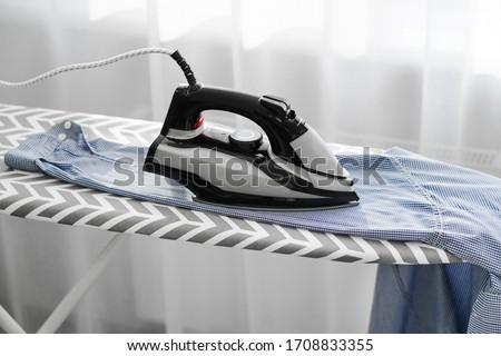 woman ironing men's blue shirt on an ironing board. Macro Royalty-Free Stock Photo #1708833355