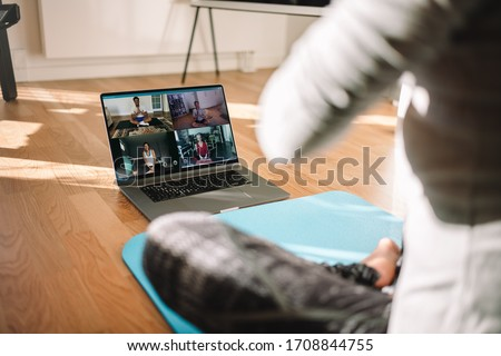 View of a woman conducting virtual fitness class with group of people at home on a video conference. Fitness instructor taking online yoga classes over a video call in laptop. #1708844755