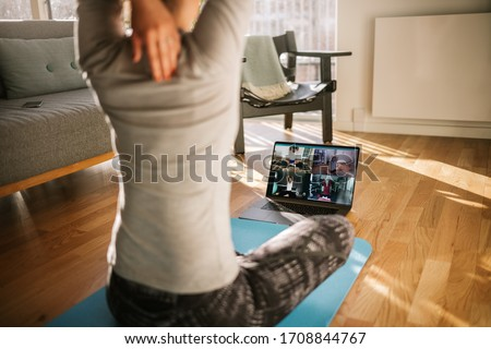 Fitness coach teaching yoga online to group of people. Yoga trainer demonstrating yoga poses to students via video conference. #1708844767