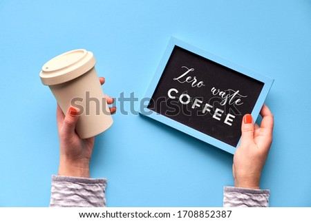 """Bamboo coffee cup, keep cup or travel mug in female hand on blue mint background. Creative flat lay, top view image, text """"reusable coffee cup"""" on black chalk board. Zero waste eco friendly keep cup #1708852387"""