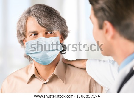 Doctor and a senior man wearing a face mask during coronavirus and flu outbreak #1708859194