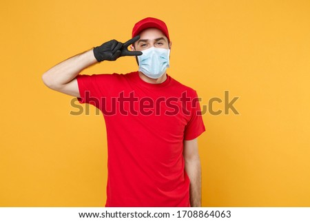 Delivery man in red cap blank t-shirt uniform sterile face mask gloves isolated on yellow background studio Guy employee working courier Service quarantine pandemic coronavirus virus concept #1708864063