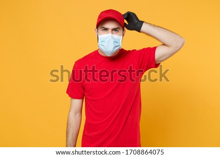 Delivery man in red cap blank t-shirt uniform sterile face mask gloves isolated on yellow background studio Guy employee working courier Service quarantine pandemic coronavirus virus concept #1708864075