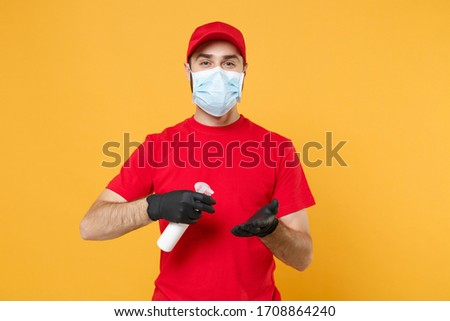 Delivery man employee in red t-shirt uniform sterile face mask glove hold bottle sanitizer soap isolated on yellow background studio Service quarantine pandemic coronavirus virus 2019-ncov concept #1708864240