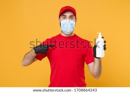 Delivery man employee in red t-shirt uniform sterile face mask glove hold bottle sanitizer soap isolated on yellow background studio Service quarantine pandemic coronavirus virus 2019-ncov concept #1708864243