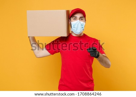 Delivery man employee in red cap blank t-shirt uniform face mask gloves hold empty cardboard box isolated on yellow background studio Service quarantine pandemic coronavirus virus 2019-ncov concept #1708864246