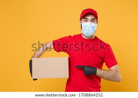 Delivery man employee in red cap blank t-shirt uniform face mask gloves hold empty cardboard box isolated on yellow background studio Service quarantine pandemic coronavirus virus 2019-ncov concept #1708864252