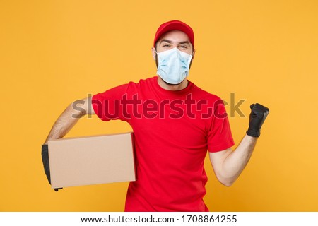 Delivery man employee in red cap blank t-shirt uniform face mask gloves hold empty cardboard box isolated on yellow background studio Service quarantine pandemic coronavirus virus 2019-ncov concept #1708864255