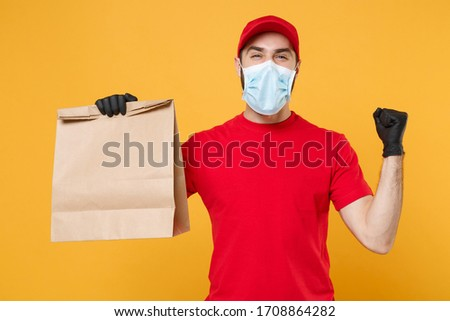 Delivery man employee in red cap t-shirt uniform mask glove hold craft paper packet with food isolated on yellow background studio Service quarantine pandemic coronavirus virus 2019-ncov concept #1708864282