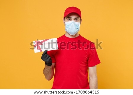 Delivery man red cap blank t-shirt uniform sterile mask gloves isolated on yellow background studio Guy employee working courier hold certificate Service pandemic coronavirus virus 2019-ncov concept #1708864315
