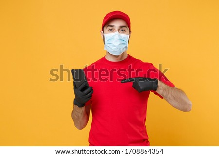 Delivery man in red cap blank t-shirt uniform sterile face mask gloves isolated on yellow background studio Guy courier hold mobile phone Service quarantine pandemic coronavirus 2019-ncov concept #1708864354