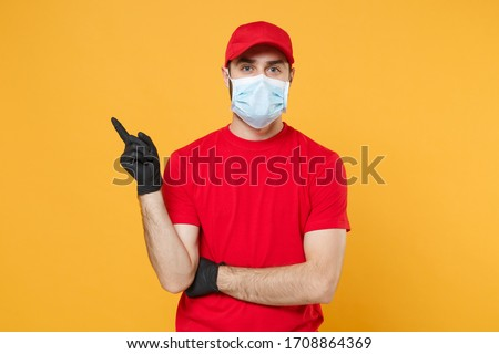 Delivery man in red cap blank t-shirt uniform sterile face mask gloves isolated on yellow background studio Guy employee working courier Service quarantine pandemic coronavirus virus concept #1708864369