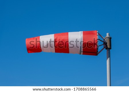 Windsock indicator of wind on runway airport. Wind cone indicating wind direction and force. Horizontally flying windsock (wind vane) with blue sky in the background #1708865566