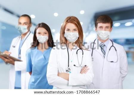 Hospital medical staff team wearing a uniform and masks #1708866547