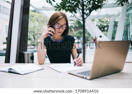 freelance Asian female in black formal wear and eyeglasses sitting at table with notepad holding pen having phone call while using laptop working remotely in workplace on background of glass wall  Royalty-Free Stock Photo #1708916416