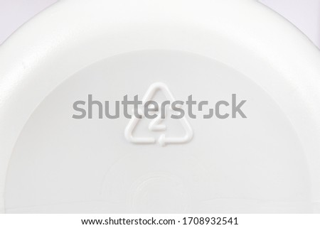 A triangle recycling icon with number 2 seen on the bottom of a plastic bottle indicating it's made of high-density polyethylene, or HDPE, a recyclable plastic material and safe for reuse. Macro view. Royalty-Free Stock Photo #1708932541