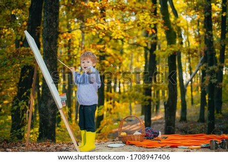 Little baby boy painting with drawing easel at fall autumn forest park background and smiling. Child pointing finger at camera. Funny happy kid. Children creativity concept