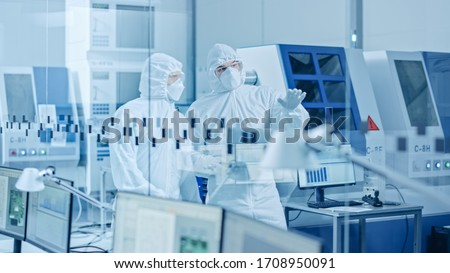Sterile Modern Factory: Professionals in Coveralls, Masks Walk Through Workshop and Talk. Medical Electronics Manufacturing Laboratory with High Tech CNC Machinery, Robot Arm Production Line Equipment #1708950091