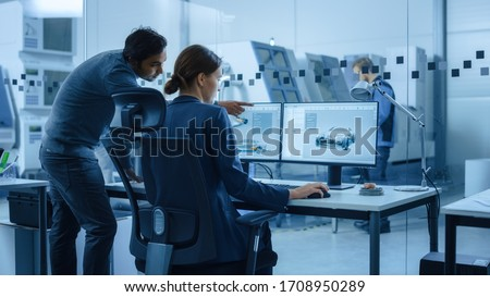 Automotive Design Factory: Project Manager and Chief Mechanical Engineer Talk, Point at Computer Display Showing 3D Electric Car Model in CAD Software. High Tech Facility with Automatic CNC Machinery Royalty-Free Stock Photo #1708950289