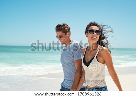 Beautiful woman with man wearing sunglasses walking on beach.. Young couple enjoying honeymoon after marriage at sea. Happy casual couple holding hands and walking at the beach with copy space. #1708961326