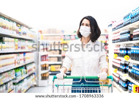 Asian woman wearing face mask and rubber glove push shopping cart in suppermarket departmentstore. Girl choosing, looking grocery things to buy at shelf during coronavirus crisis or covid19 outbreak. #1708963336