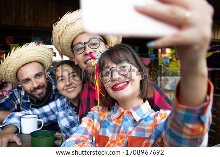 Festa Junina in Brazil, known as brazilian June Festival. Young woman and Joyful Friends wearing traditional junina costume take a selfie at Arraial Party. Good times and happiness concept.