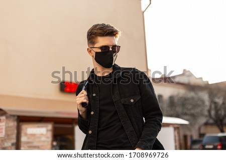 Handsome young hipster man with hairstyle in trendy sunglasses in fashionable black denim jacket in stylish medical black mask walks on street on sunny day. Attractive guy model. Fashion 2020. Spring. #1708969726