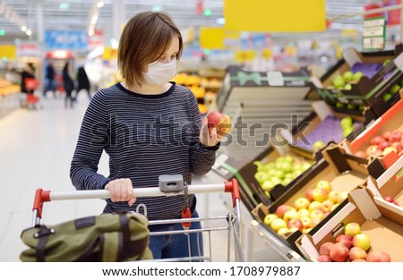 Young woman wearing disposable medical mask shopping in supermarket during coronavirus pneumonia outbreak. Protection and prevent measures while epidemic time. #1708979887