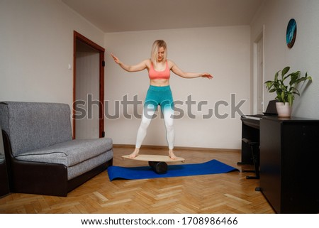 Isolated women on Deck for balance board. Rocker-roller boards. Isolated oval wooden deck for balance board. Young smiling women keeping balance on the wooden board.Rocker-roller boards.  #1708986466