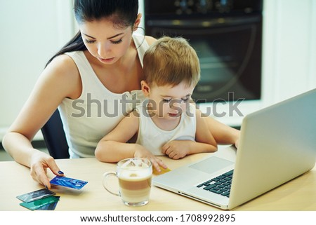 Mother with child working at the computer at home. remote work #1708992895