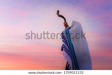 Blowing the Shofar - man in a tallith, Jewish prayer shawl is blowing the shofar ram's horn Royalty-Free Stock Photo #1709011132