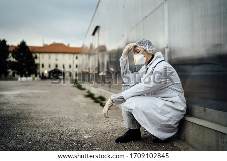 Depressed crying doctor with mask having mental breakdown.Fear,anxiety,panic attack due to coronavirus outbreak.Psychological effects of COVID-19.PTSD.Mental health,coping with death #1709102845