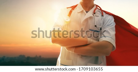 Doctor wearing facemask and superhero cape during coronavirus outbreak. Virus and illness protection, quarantine. COVID-2019. Super hero power for  medicine. Person on sunset cityscape background. Royalty-Free Stock Photo #1709103655