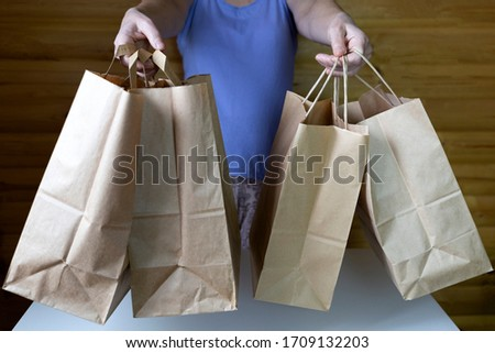 Woman holding many brown carton paper bags. Lots of purchases after shopping. Consumerism concept. #1709132203