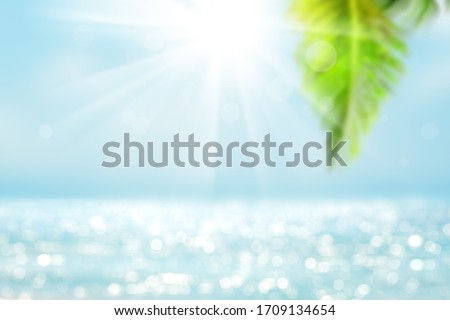 Blurred blue sky and sea with bokeh light and leaves of coconut palm tree. Landscape of tropical summer. Summer vacation concept. #1709134654