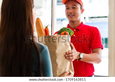 Delivery man sending food and vegetables in paper bag or paper container to recipient at the door. Food delivery, shopping online and transport concept #1709163811